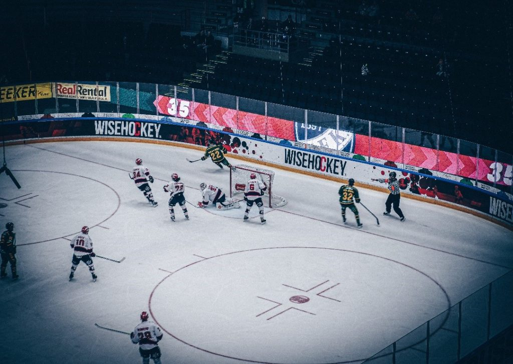 Players in a hockey rink with real-time data on LED screens