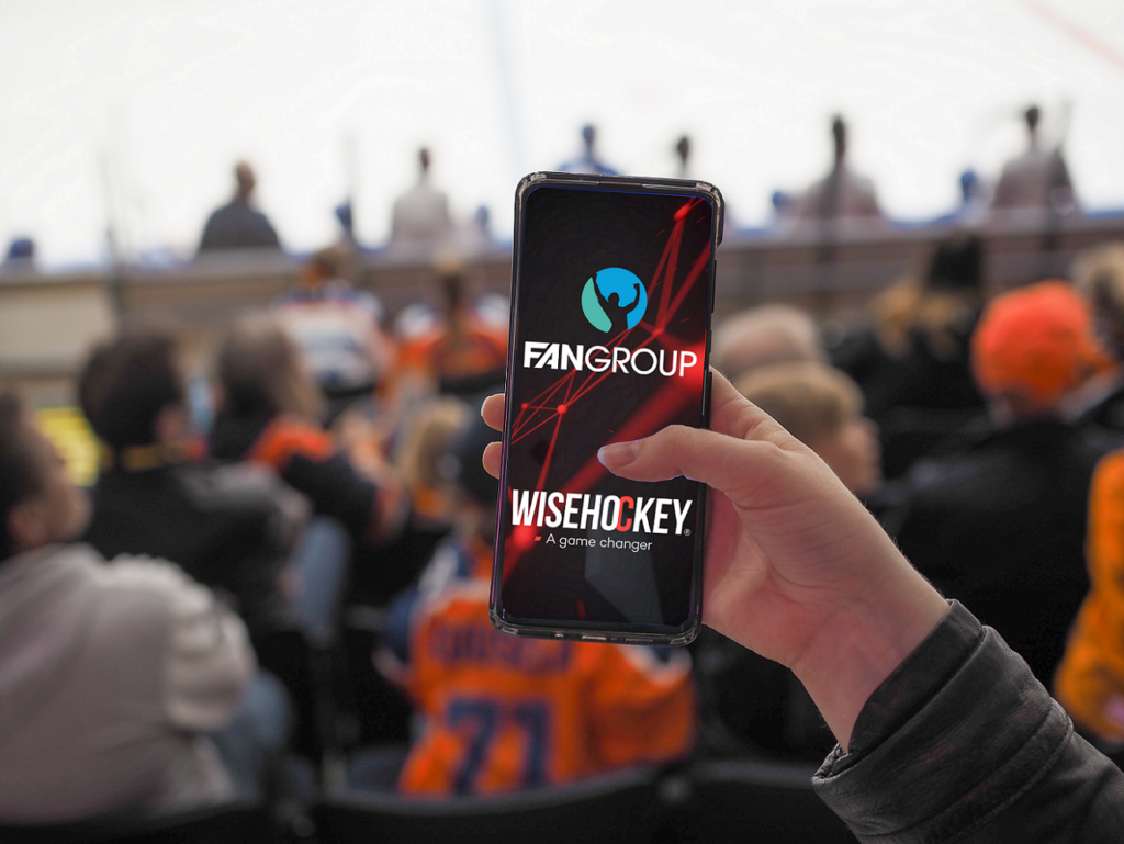 Mobile phone in a fan's hand showing Wisehockey's and The Fan Group's logos